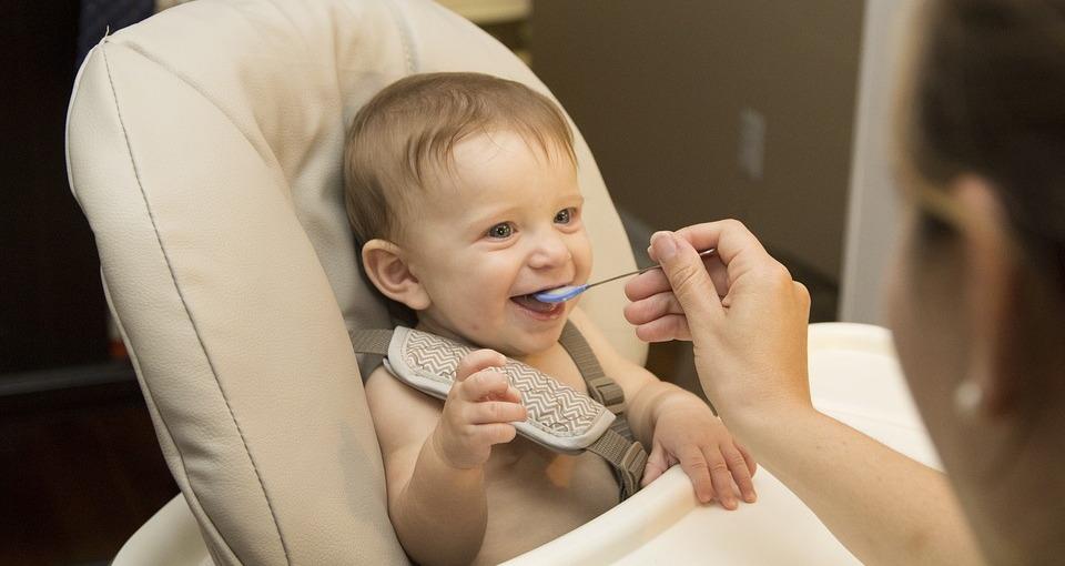Мать кормит малыша с ложки