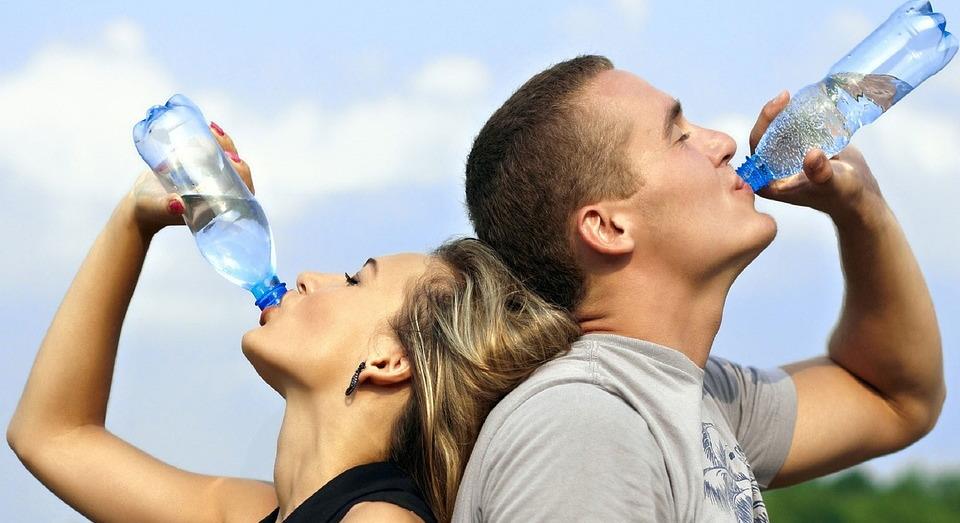 Мужчина и женщина пьют воду из бутылок