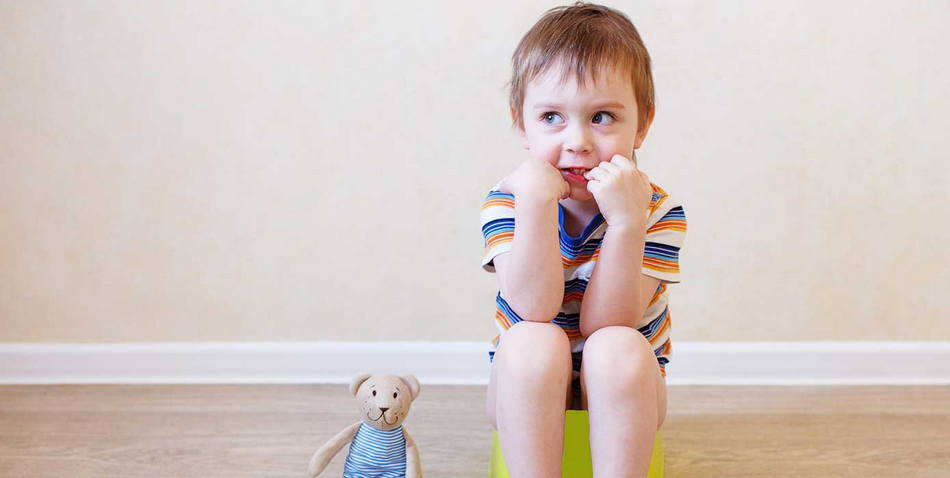 Ребенок четырех лет сидит на горшке