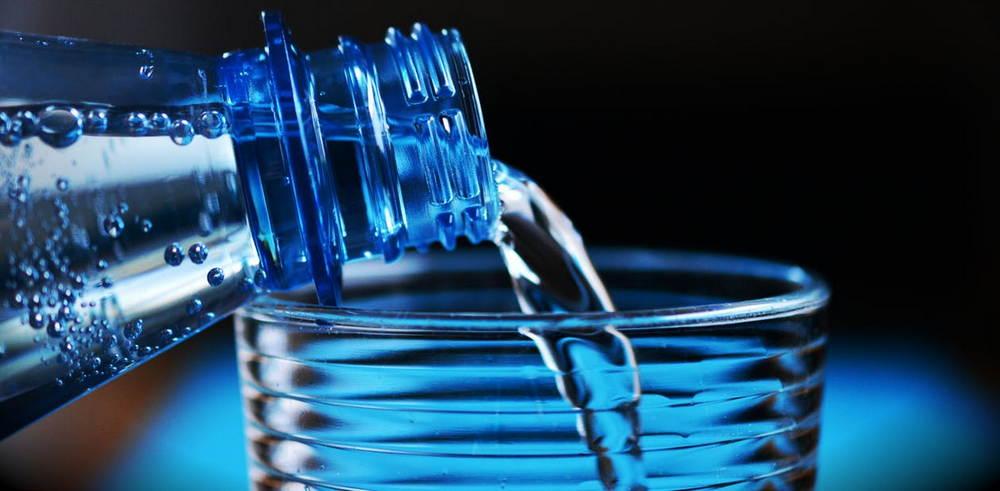 минеральная вода из бутылки льется в стакан
