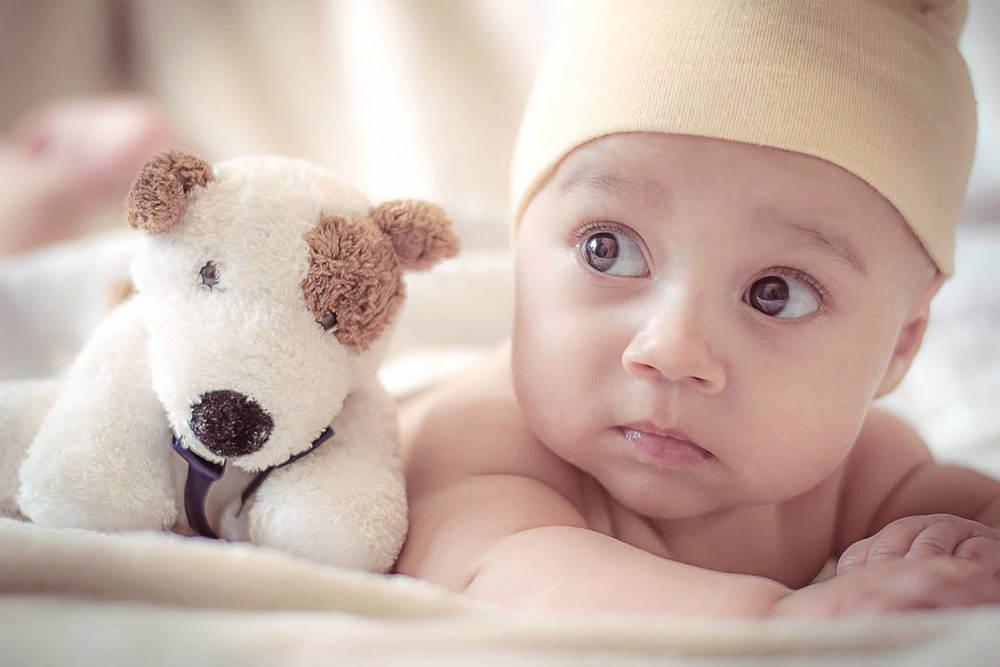 Грустный грудной ребенок с игрушкой